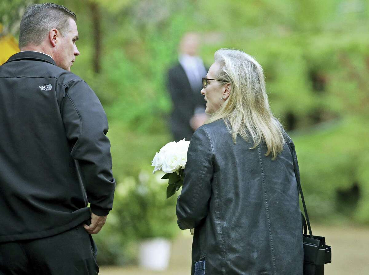 """Actress Meryl Streep arrives with flowers at a memorial service at the homes of Debbie Reynolds and her daughter Carrie Fisher in Los Angeles Thursday, Jan. 5, 2017. Reynolds died Dec. 28 at the age of 84, a day after her daughter died at the age of 60. Streep starred in the film, """"Postcards From the Edge,"""" based on Fisher's 1987 semi-autobiographical novel of the same title."""