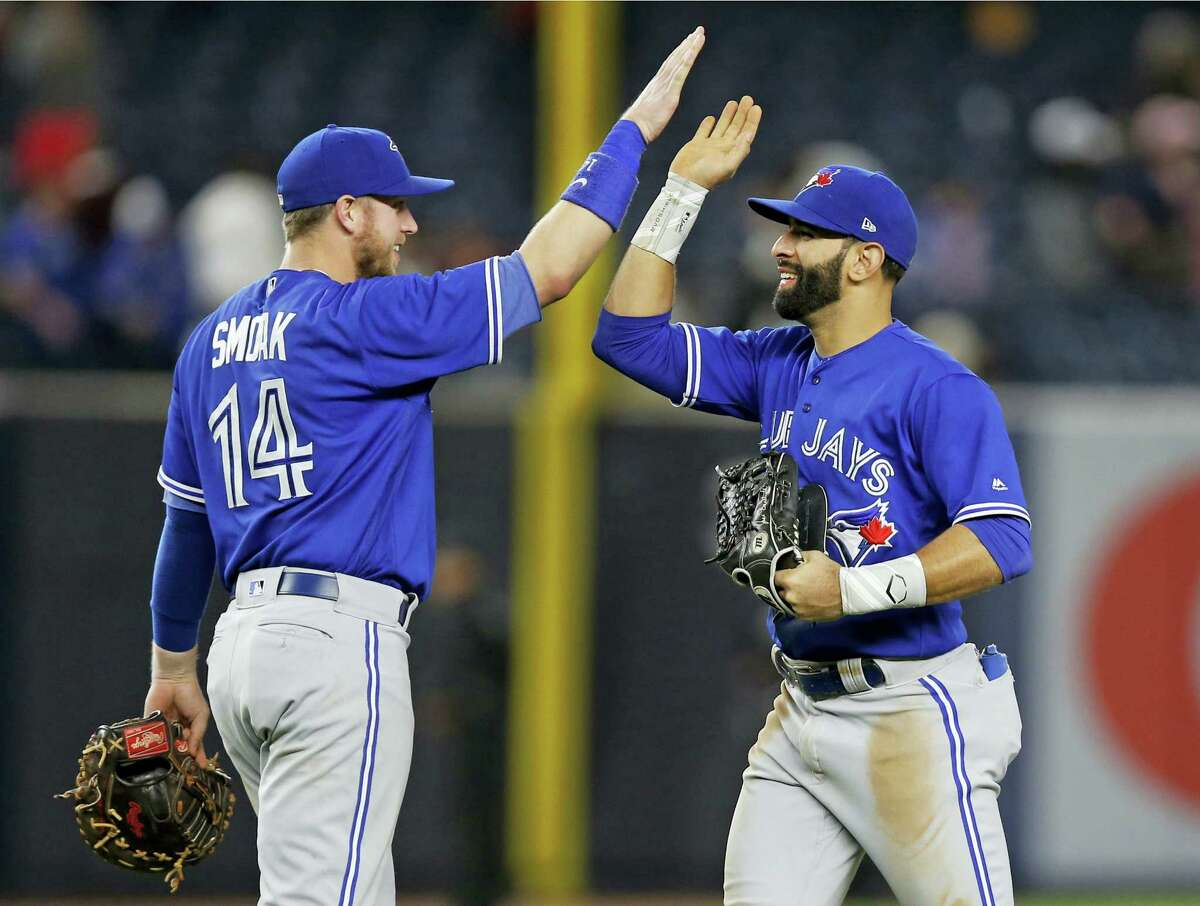 Toronto Blue Jays first baseman Justin Smoak (14) and Blue Jays right fielder Jose Bautista celebrate after the Blue Jays 7-1 defeat of the New York Yankees in a baseball game in New York, Monday.