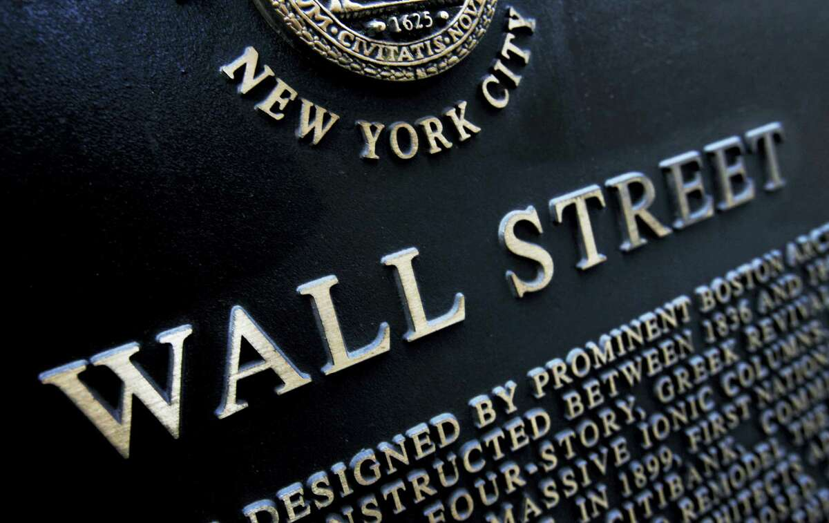 FILE - This Jan. 4, 2010, file photo shows an historic marker on Wall Street in New York. On Thursday, April 27, 2017, global stocks were subdued as investors assessed the scant details of President Donald Trump's U.S. tax overhaul.