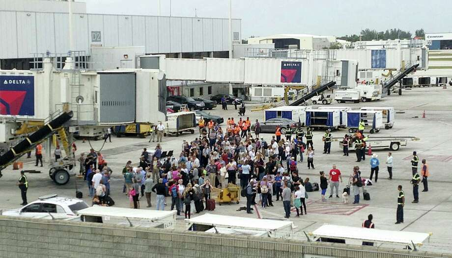 People stand on the tarmac at the Fort Lauderdale-Hollywood International Airport after a shooter opened fire inside a terminal of the airport, killing at least five people and wounding others before being taken into custody, Friday, Jan. 6, 2017, in Fort Lauderdale, Fla. Photo: Wilfredo Lee — AP Photo / Copyright 2017 The Associated Press. All rights reserved.
