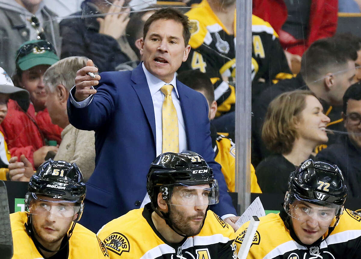 In this file photo, Boston Bruins interim head coach Bruce Cassidy works behind the bench in the third period of an NHL hockey game against the Washington Capitals. The Bruins said on Wednesday it will drop the interim tag and Cassidy will return next season as the team's head coach. Cassidy replaced Claude Julien in February and helped the team return to the playoffs for the first time in three seasons.