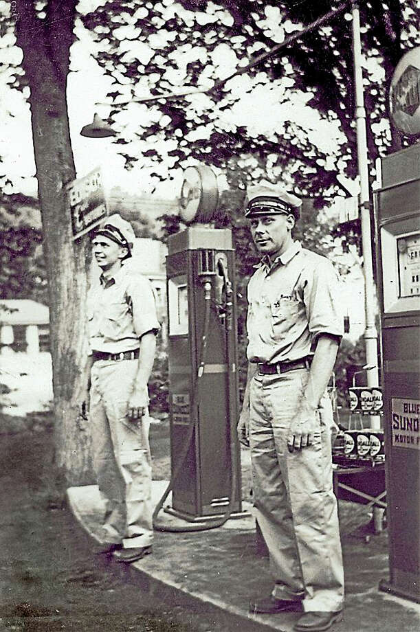 Stanley and Elmer Gunnarson stand at the gas pumps in front of Gunnarson's Garage on School Street in Washington Depot, circa 1932. Photo:  Photograph From The Collection Of The Gunn Historical Museum