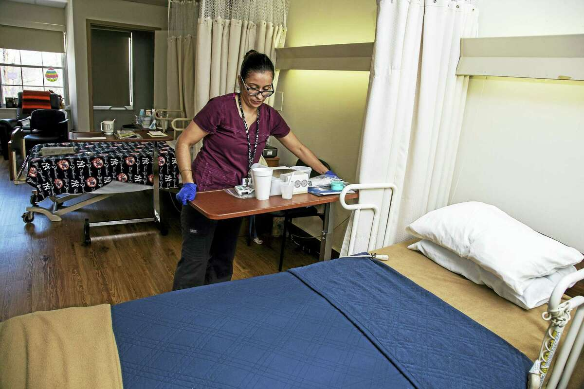 60 West nurse Irene Rivera, LPN, cleans a patient's room at the Rocky Hill nursing home.