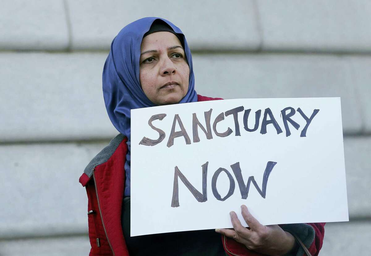 In this Jan. 25, 2017 photo, Moina Shaiq holds a sign at a rally outside of City Hall in San Francisco. On Tuesday, April 25, 2017, a federal judge blocked a Trump administration order to withhold funding from communities that limit cooperation with U.S. immigration authorities, saying the president has no authority to attach new conditions to federal spending.