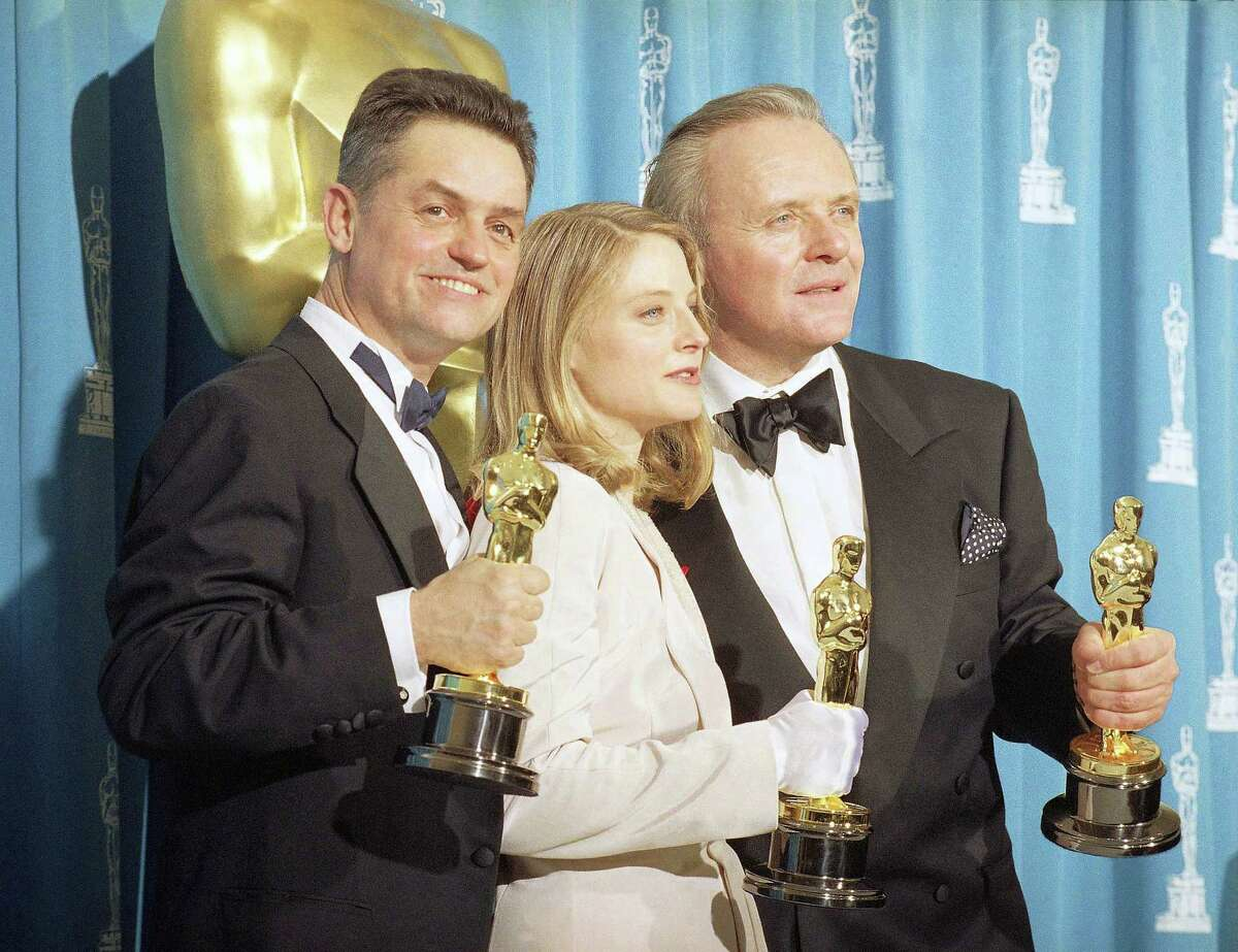 """In this May 31, 1992, file photo, director Jonathan Demme, left, holds his award for best director, actress Jodie Foster holds her award for best actress, and actor Anthony Hopkins holds his award for best actor for their work on """"Silence of the Lambs,"""" at the Academy Awards in Los Angeles. Demme died, Wednesday, April 26, 2017, from complications from esophageal cancer in New York. He was 73."""