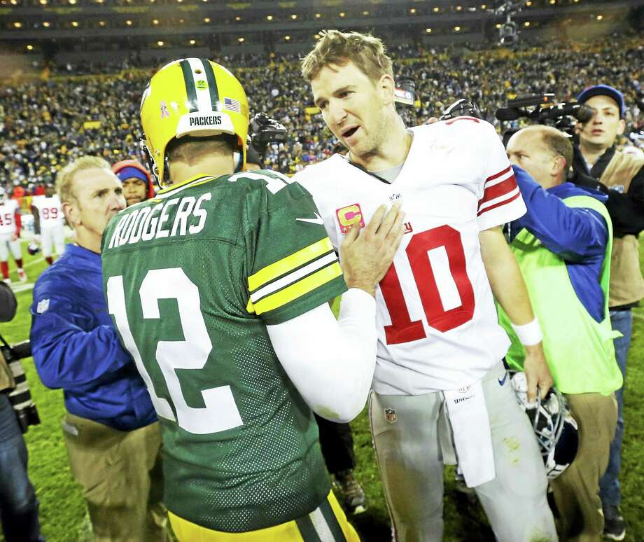 The Packers' Aaron Rodgers talks to Giants quarterback Eli Manning after a game earlier this season. Photo: The Associated Press File Photo  / FR155603 AP