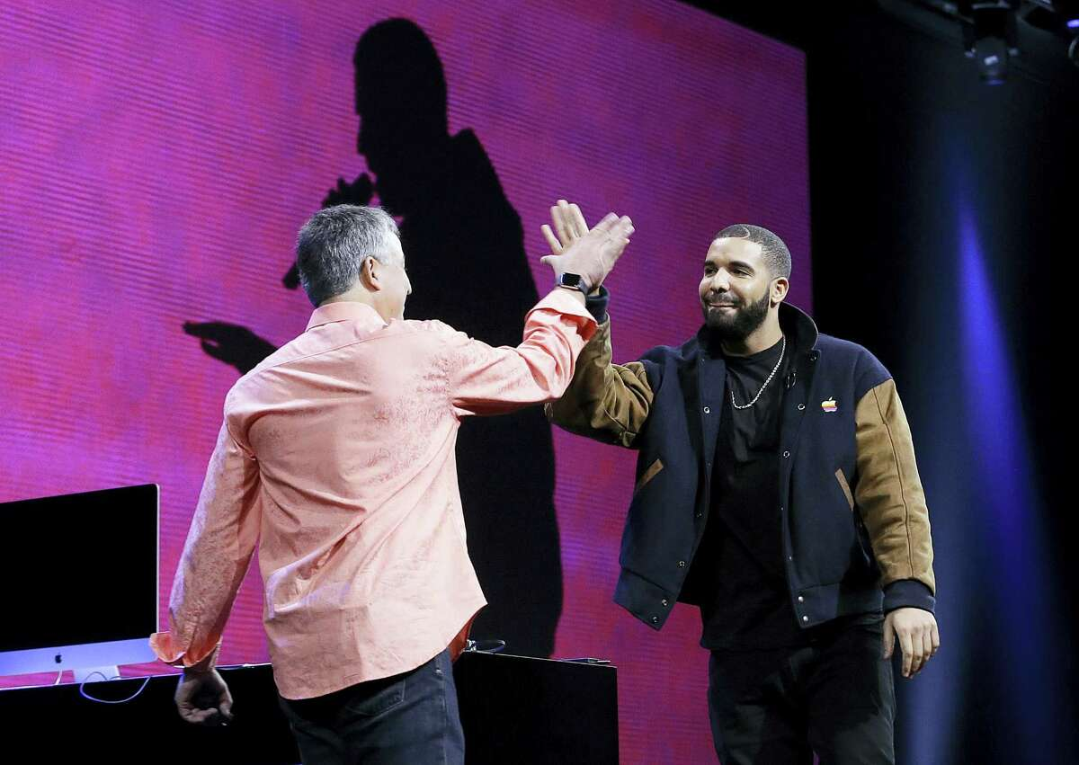 Musician Drake, right, high fives Eddy Cue, Apple senior vice president of Internet Software and Services, during the Apple Worldwide Developers Conference in San Francisco on Monday, June 8, 2015.