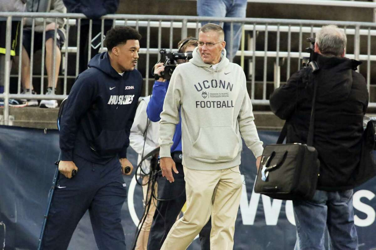 Injured player E.J. Levenberry talks with UConn football coach Randy Edsall before the NCAA college football team's spring game last Friday at rentschler Field. Edsall is looking forward to playing Boston College at Fenway Park in November in what is considered one of the Huskies' home games.