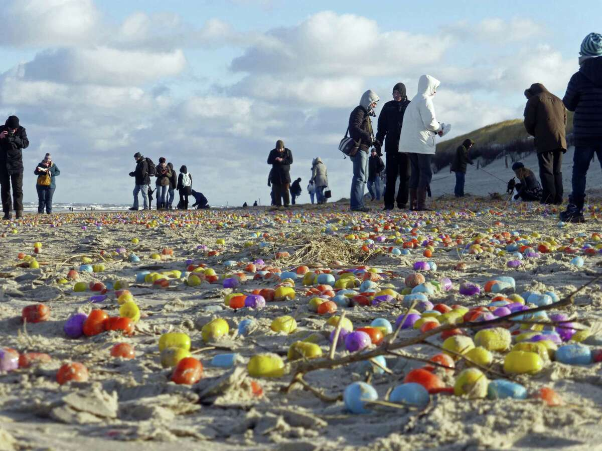 Tourists gather colorful plastic eggs on the beach of the German North Sea island of Langeoog, Thursday Jan. 5, 2017. Easter has come early to the German North Sea island of Langeoog. A flood of plastic eggs containing tiny toys has been swept ashore after a fierce storm, to the delight of the island's youngest residents. The eggs containing instructions in the Cyrillic alphabet appear to have come from a container lost by a cargo ship en route for the German port of Bremerhaven.