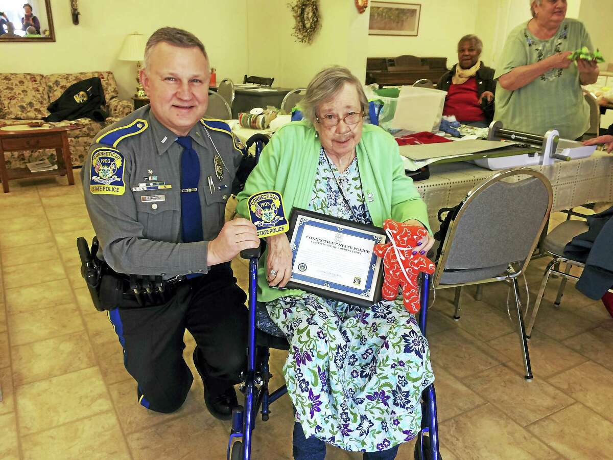 Lt. William R. Baldwin Jr., commander of State Police Troop B in North Canaan, recently presented Pearl Lovgreen with a certificate of appreciation for her group's work, making teddy bears to comfort people in need in the northwest corner.