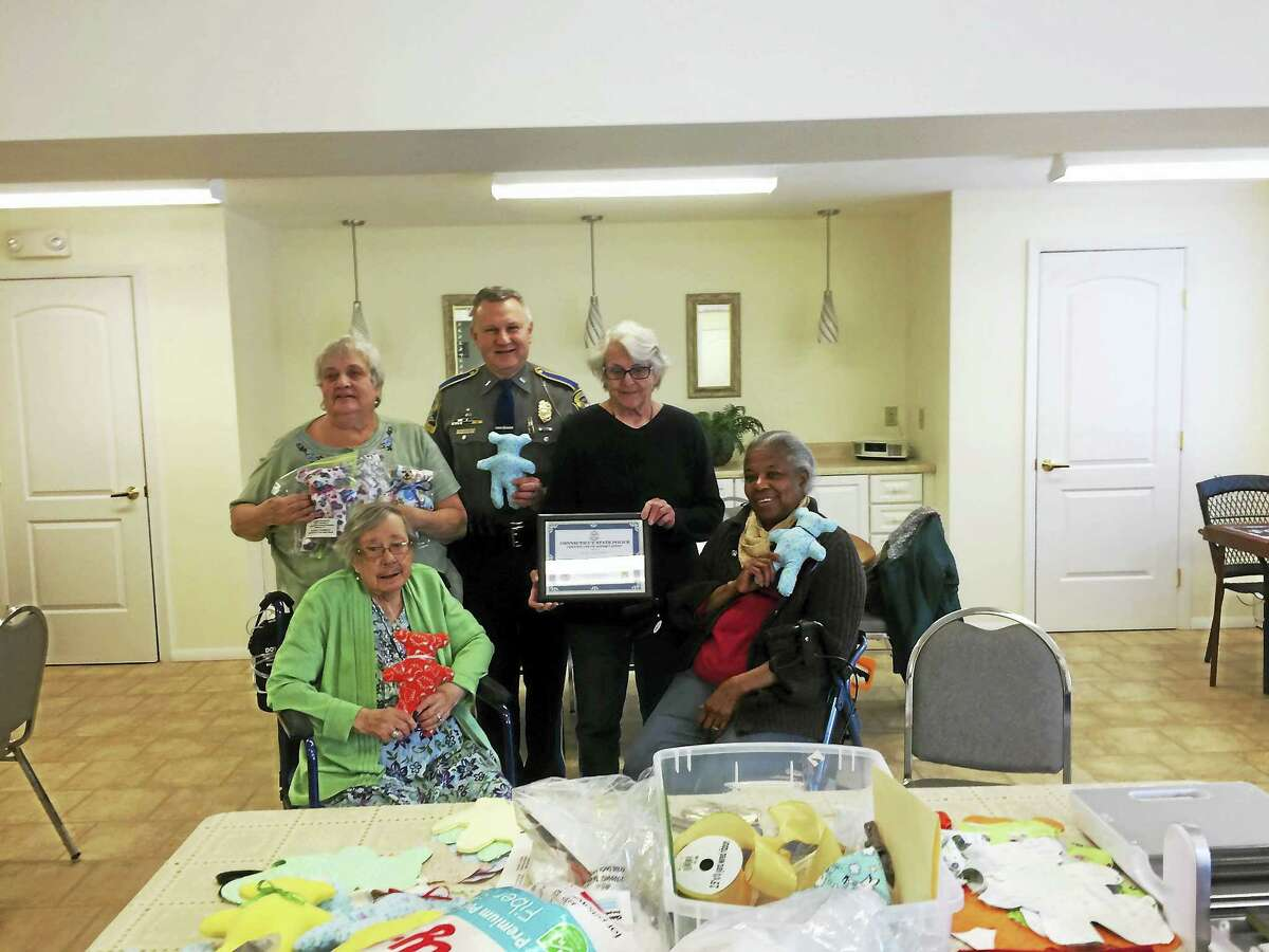 A group of women at Meadowbrook in Norfolk have made more than 1,000 teddy bears, which are distributed to people in need. Lt. William R. Baldwin Jr., commander of State Police Troop B in North Canaan, recently presented the group's leader, Pearl Lovgreen, with a certificate of appreciation for her group's work. In the photo, Baldwin, standing in the center, is joined by Lovgreen, seated, left, Linda Holst-Grubbe, standing, right, Phylis Bernard, left, and Mary Ford-Bey, seated, right.