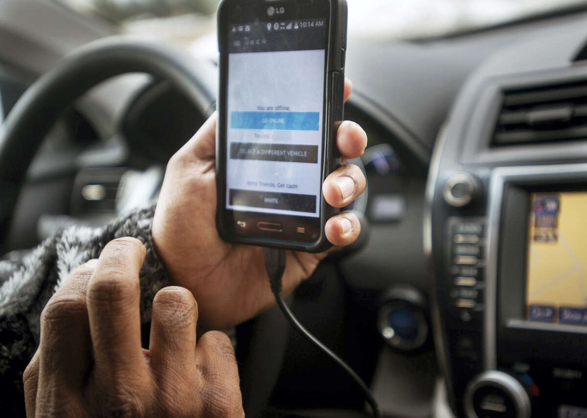 Mohammad Uddin checks his smartphone he uses to provide rides via the Uber app.