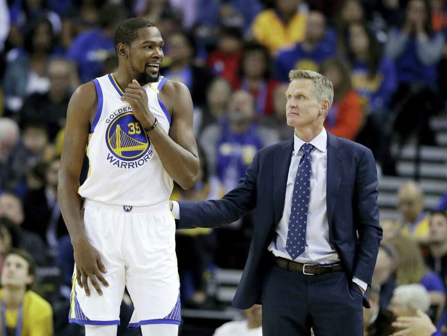 In this Nov. 23, 2016 photo, Golden State Warriors' Kevin Durant, left, talks with coach Steve Kerr during the team's NBA basketball game against the Los Angeles Lakers in Oakland, Calif. Durant won't play later Saturday, April 22, 2017 in Game 3 against the Portland Trail Blazers because of a strained left calf. The Warriors will also be without Kerr because of an illness. Mike Brown will serve as acting coach. Photo: AP Photo — Marcio Jose Sanchez, File  / Copyright 2016 The Associated Press. All rights reserved.