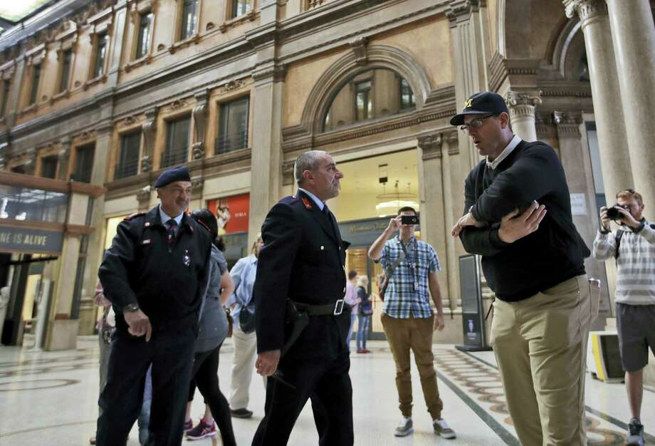 Private security guards warn Michigan coach Jim Harbaugh not to play inside the gallery during a team visit to the Alberto Sordi Gallery in central Rome on Monday. Photo: Alessandra Tarantino — The Associated Press  / Copyright 2017 The Associated Press. All rights reserved.