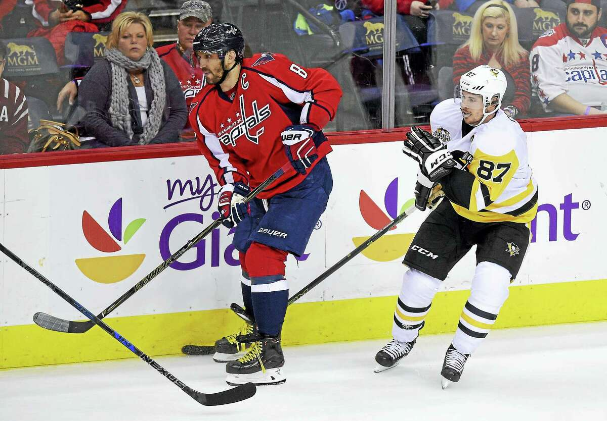 Washington Capitals left wing Alex Ovechkin (8), skates in front of Penguins center Sidney Crosby.