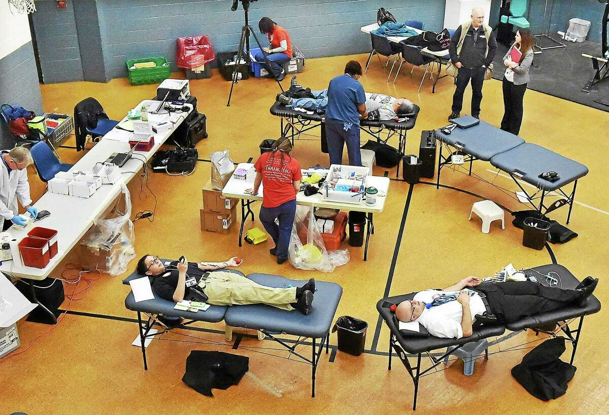 Current and retired members of the New Haven Police Department donate blood at an American Red Cross blood drive held in memory of Sergeant Dario Aponte in 2014, at the New Haven Police Department gym.