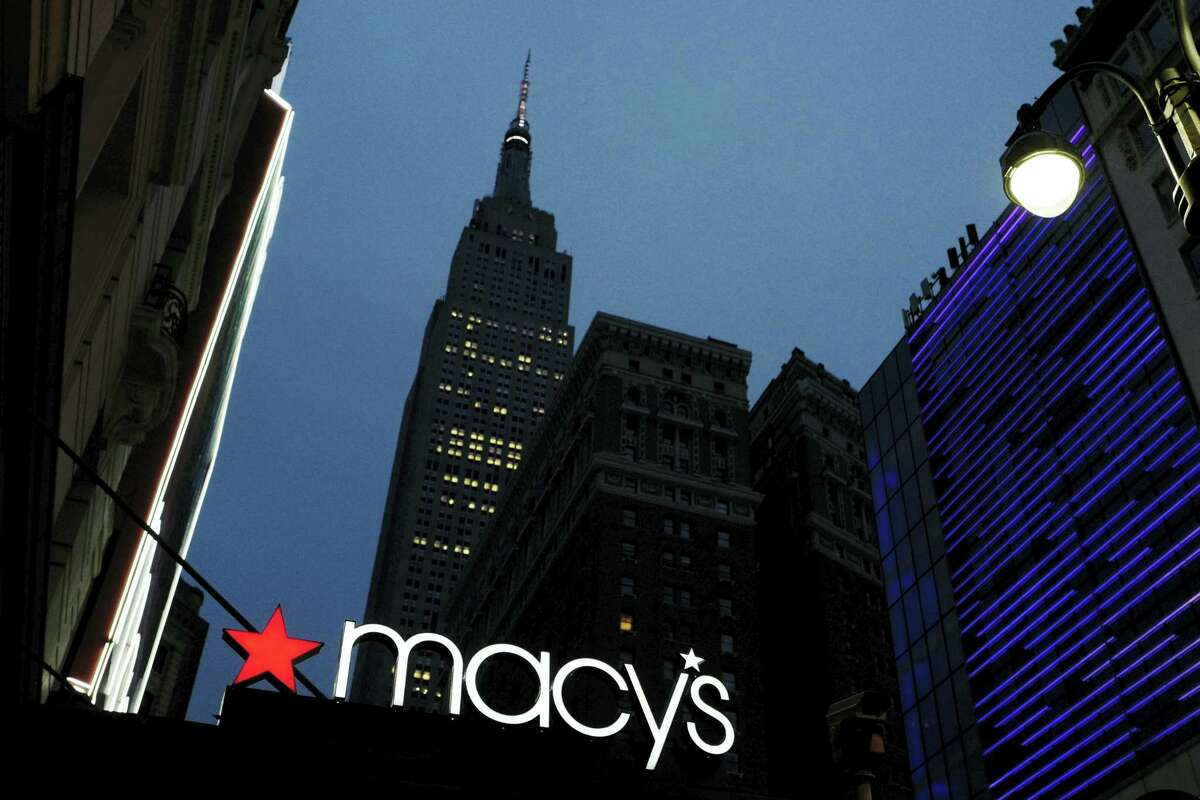 A Macy's sign being illuminated on a store marquis, in New York. Macy's says it is eliminating more than 10,000 jobs and plans to move forward with 68 store closures after a disappointing holiday shopping season. The department store chain also lowered its full-year earnings forecast.