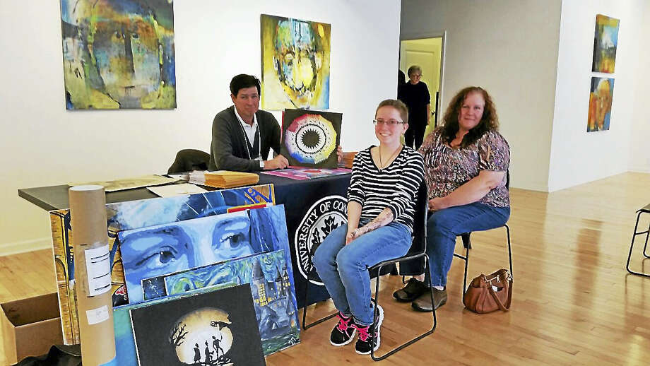 Frank Noelker, a photography professor at the University of Connecticut evaluates the art of Macayla Muzzulin, 15, of Torrington, and of Sandy Benge of Colebrook at the third annual Portfolio Day at Five Points Gallery at 33 Main Street in Torrington on Saturday morning. Representatives from three area art colleges gave feedback and information to young and old aspiring artists. The gallery also gave tours to its new Launchpad space next door at 5 Water Street, which offers shared art studio space and mentorship to 16 participating area artists. Photo: Photo By N.F. Ambery