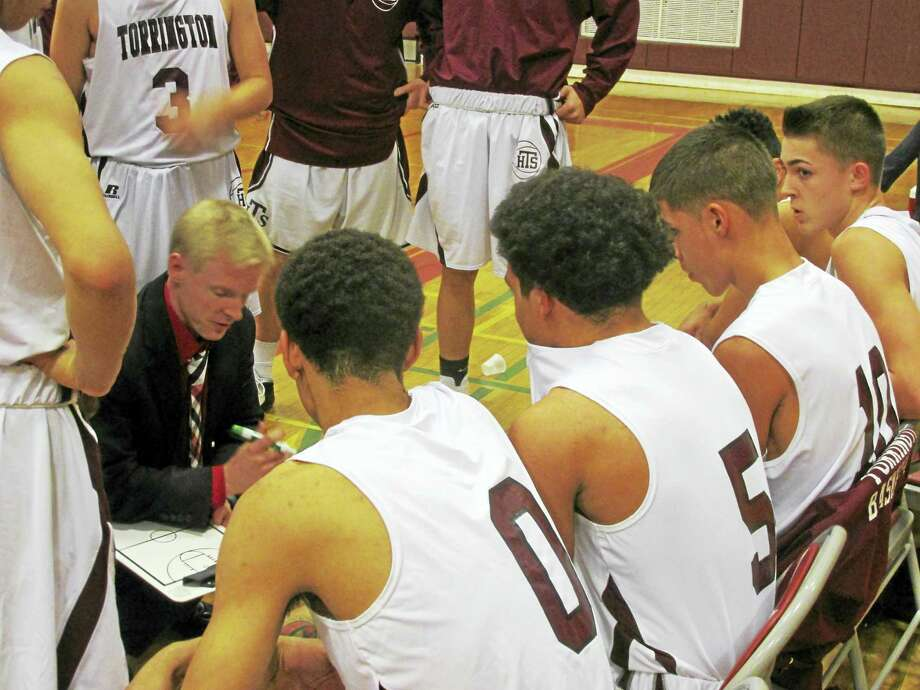 Torrington boys basketball coach Eric Gamari maps strategy for one platoon while another waits for its call in the Red Raiders' win over Wolcott Tuesday night at Torrington High School. Photo: Photo By Peter Wallace