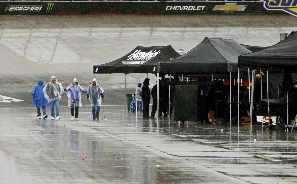 Fans walk down pit road in the rain on Sunday in Bristol, Tenn.