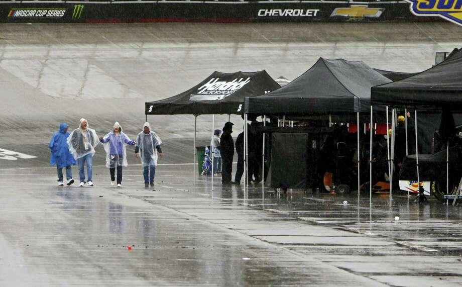 Fans walk down pit road in the rain on Sunday in Bristol, Tenn. Photo: Wade Payne — The Associated Press  / FR23601 AP