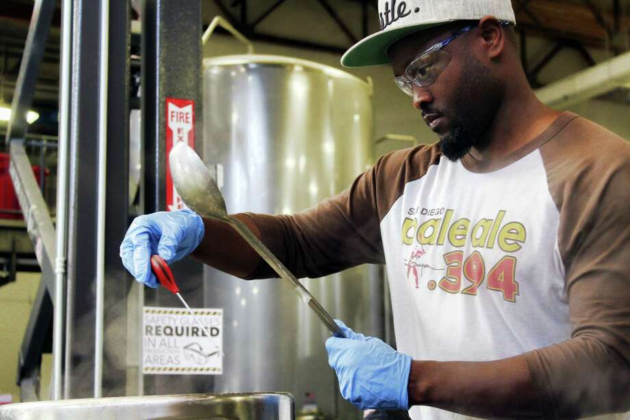 In this photo provided by AleSmith, Tony Gwynn Jr. wears safety goggles as he waits for the right moment to add hops to a boil kettle as he tweaks his craft beer recipe. Photo: Elvin Piring — AleSmith Via AP  / Elvin Piring
