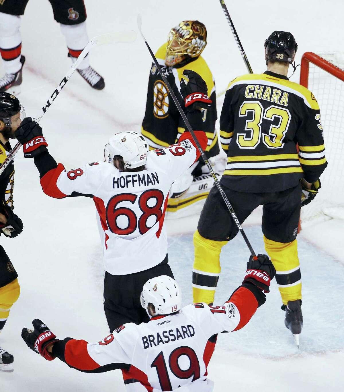 Bruins goalie Tuukka Rask, top, kneels on the ice as members of the Senators celebrate the game-winning goal on Sunday.