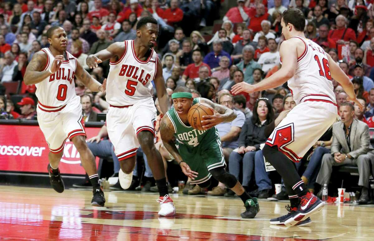 The Celtics' Isaiah Thomas (4) dribbles through the Bulls defense during the first half in Game 4 on Sunday.