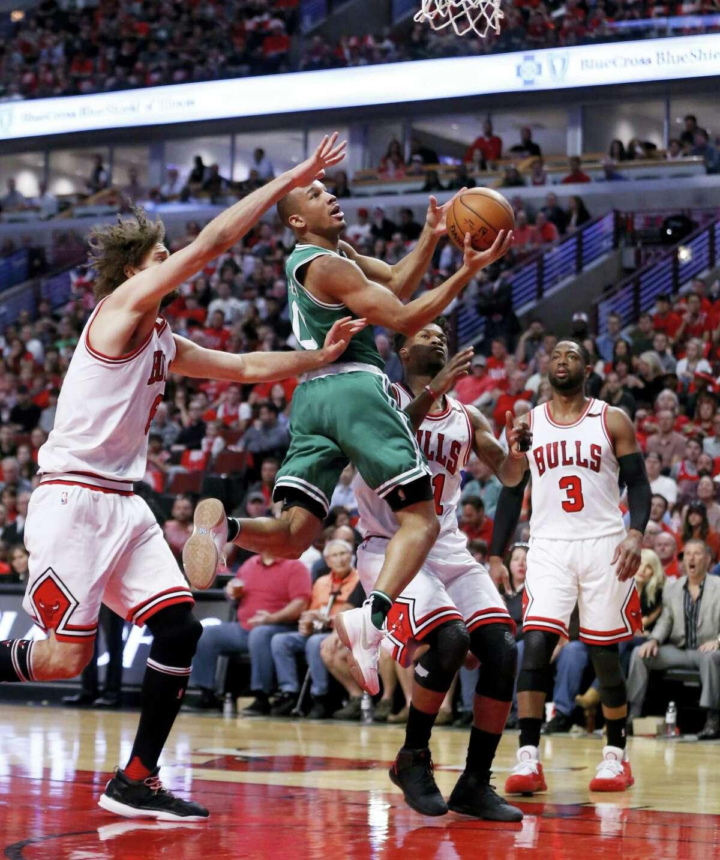 The Celtics' Avery Bradley, center, drives between Bulls' defenders on Sunday.