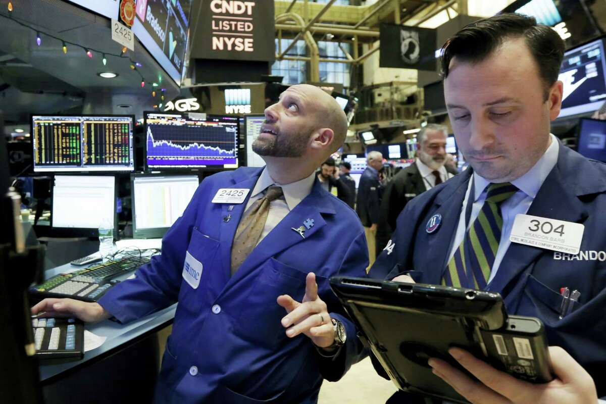 Specialist Meric Greenbaum, left, works at his post on the floor of the New York Stock Exchange Tuesday.