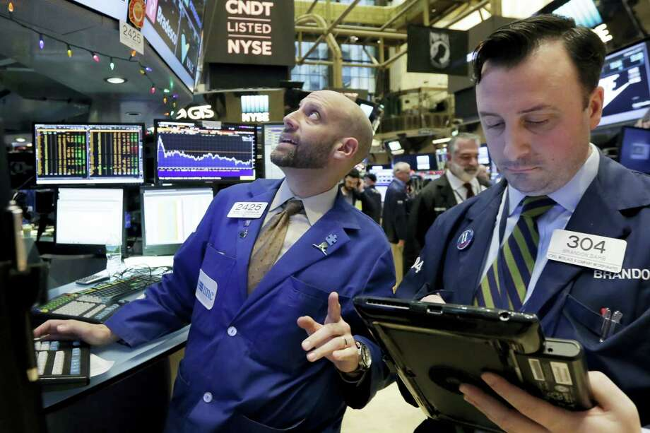 Specialist Meric Greenbaum, left, works at his post on the floor of the New York Stock Exchange Tuesday. Photo: Richard Drew — The Associated Press  / AP
