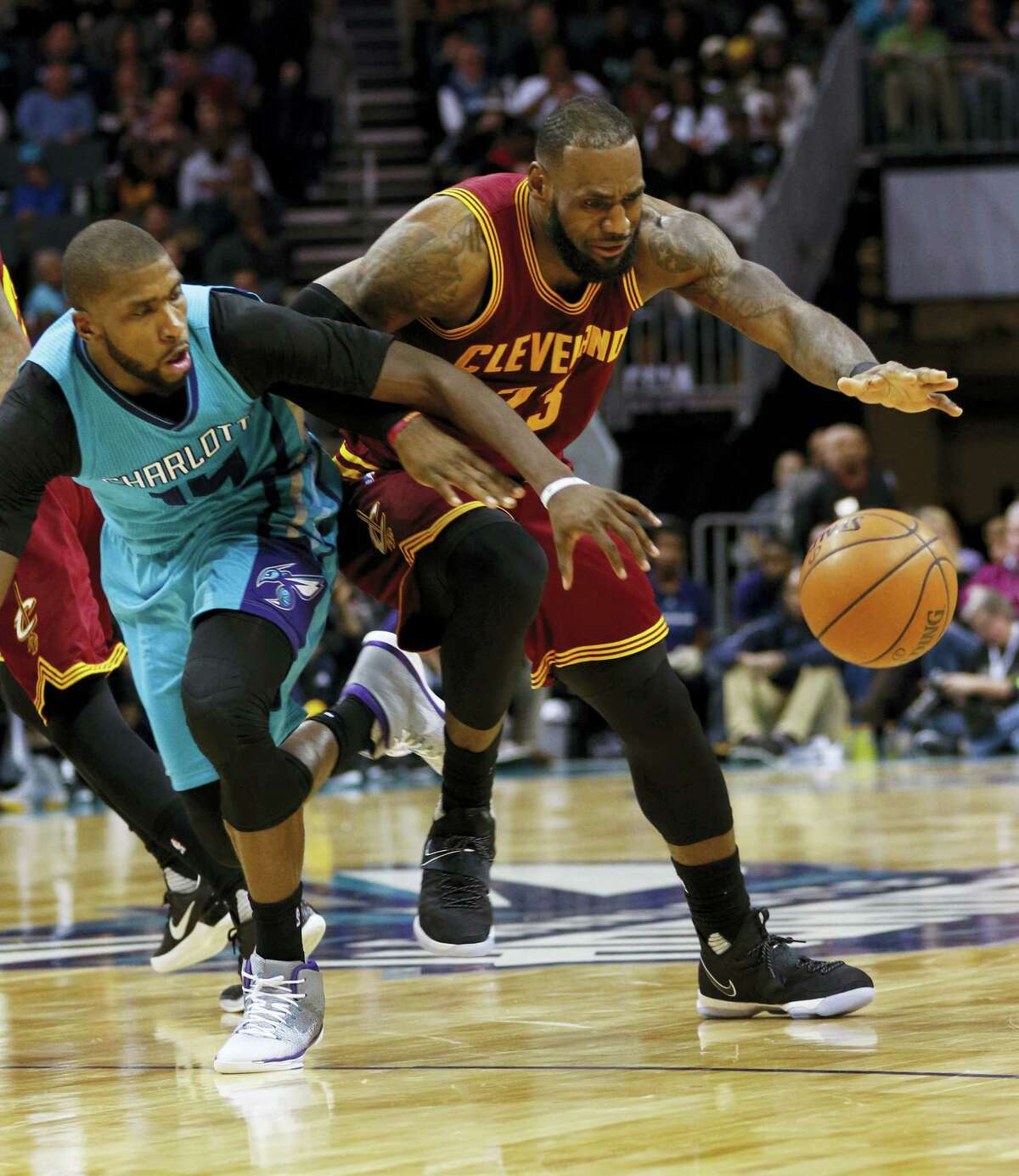 Cleveland Cavaliers forward LeBron James, right, keeps the ball from Charlotte Hornets forward Michael Kidd-Gilchrist in the second half of an NBA basketball game in Charlotte, N.C. on Dec. 31, 2016. Cleveland won 121-109.