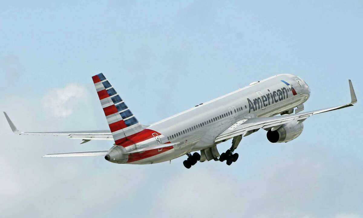 In this June 3, 2016 photo, an American Airlines passenger jet takes off from Miami International Airport in Miami. The company said it grounded a flight attendant who got into a verbal confrontation with a passenger after taking a baby stroller away from another passenger on an April 21, 2017 flight from San Francisco to Dallas-Fort Worth.
