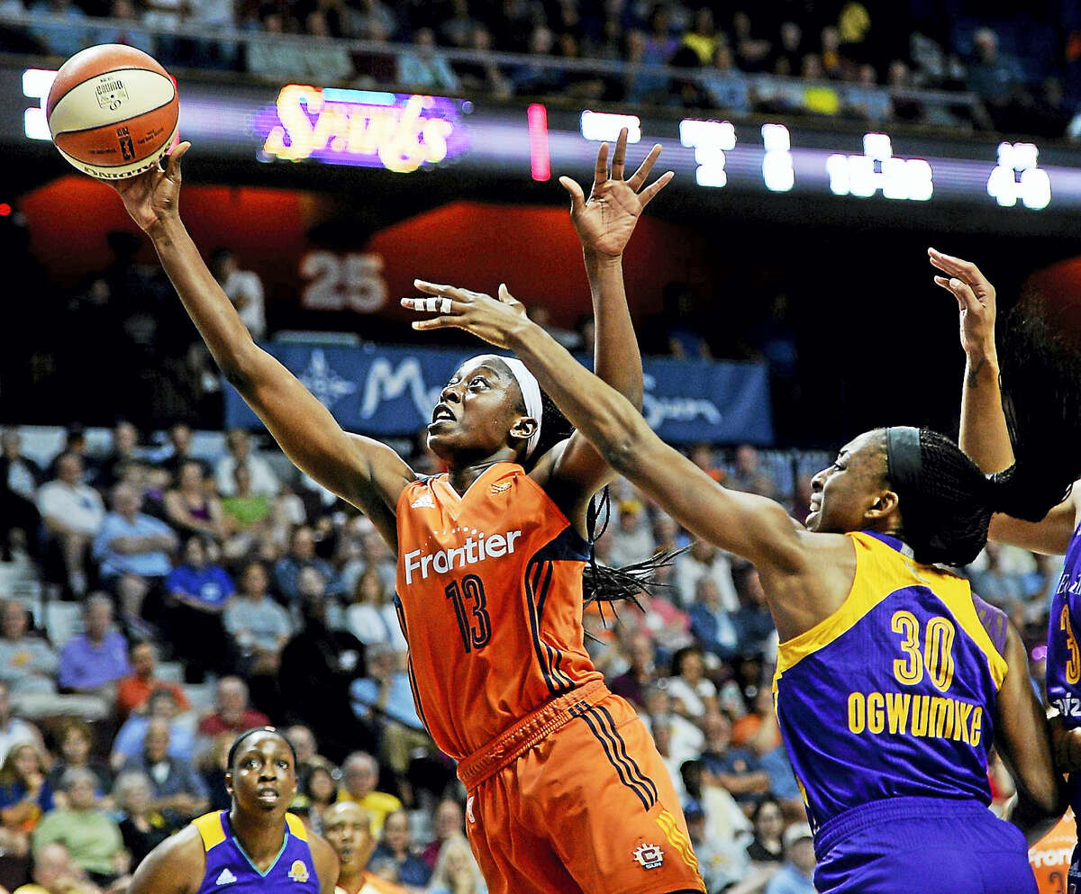 The Connecticut Sun's Chiney Ogwumike, left, shoots past the Sparks' Nneka Ogwumike during a WNBA game.