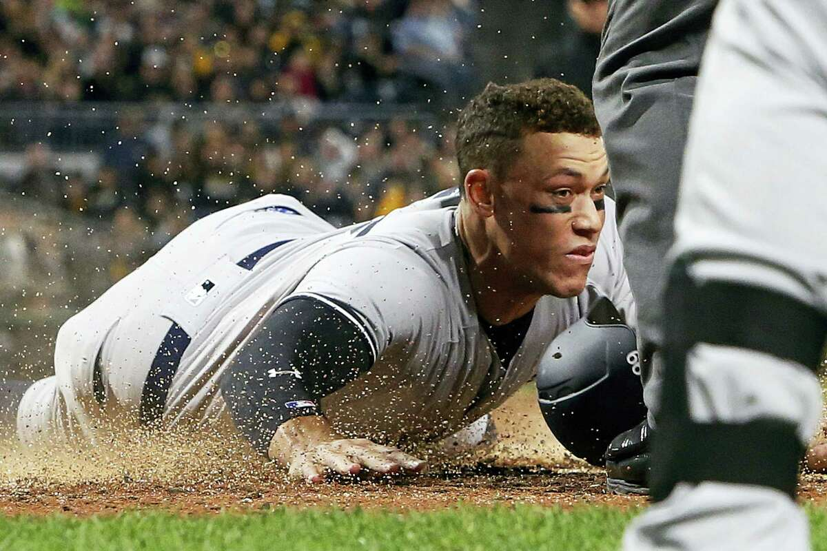 The Yankees' Aaron Judge, left, scores in the fifth inning Friday in Pittsburgh.