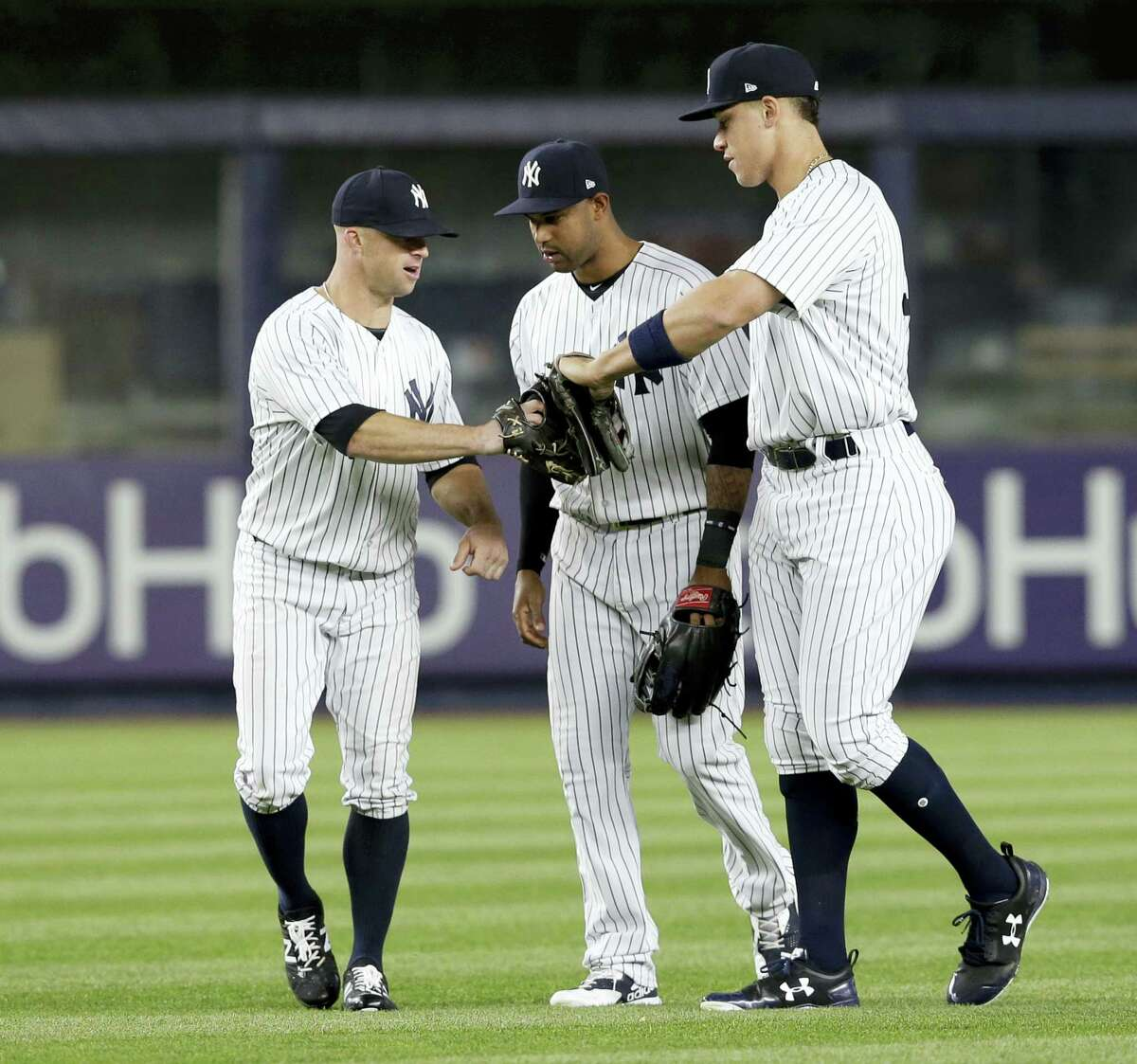 New York Yankees' Brett Gardner, left, Jacoby Ellsbury, center, and Aaron Judge celebrate in the outfield after the baseball game against the Chicago White Sox at Yankee Stadium, Wednesday, April 19, 2017, in New York. The Yankees defeated the White Sox 9-1. (AP Photo/Seth Wenig)