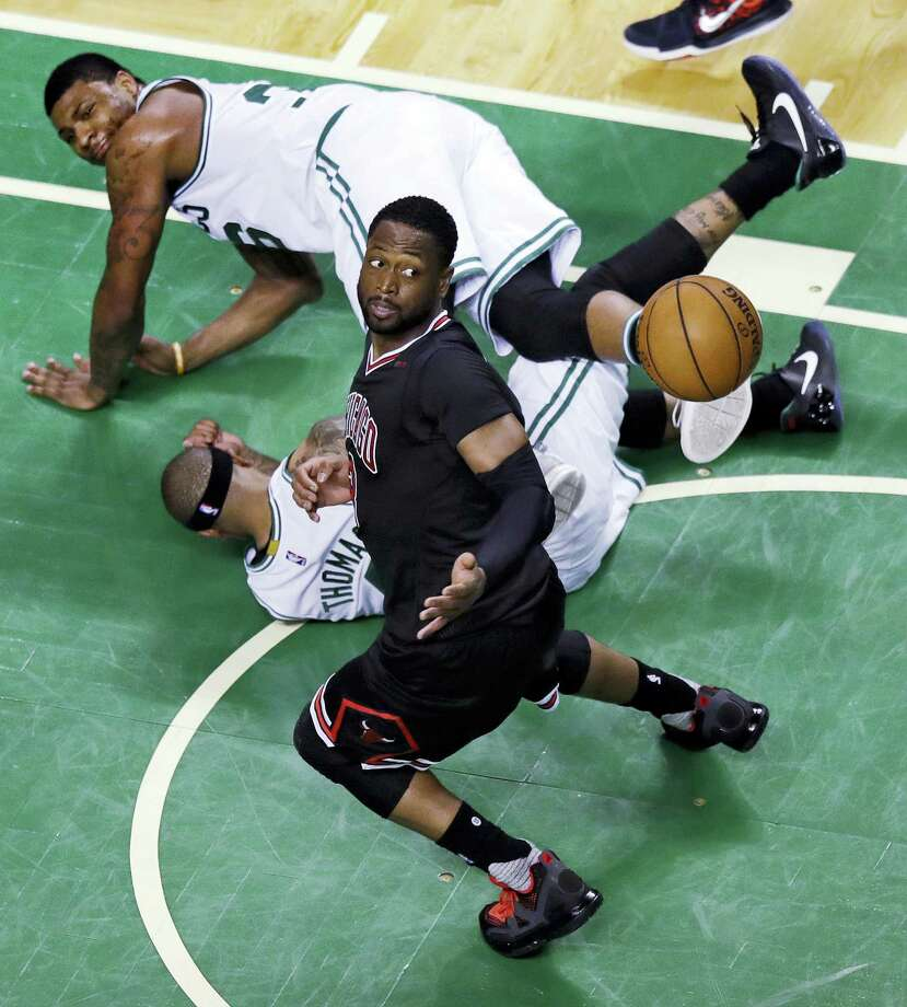 Chicago Bulls guard Dwyane Wade eyes the loose ball as Boston Celtics guards Isaiah Thomas and Marcus Smart, top, land on the floor during the fourth quarter of a first-round NBA playoff basketball game in Boston, Tuesday, April 18, 2017. The Bulls defeated the Celtics 111-97 and take a 2-0 lead in the series. (AP Photo/Charles Krupa) Photo: AP / Copyright 2017 The Associated Press. All rights reserved.
