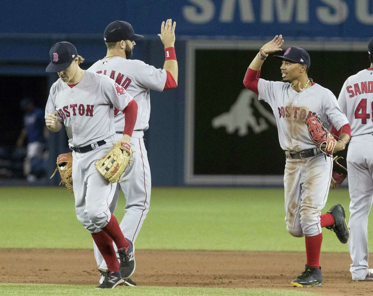Red Sox outfielder Mookie Betts, right, gets high-fives from teammates after Thursday's win over the Blue Jays.