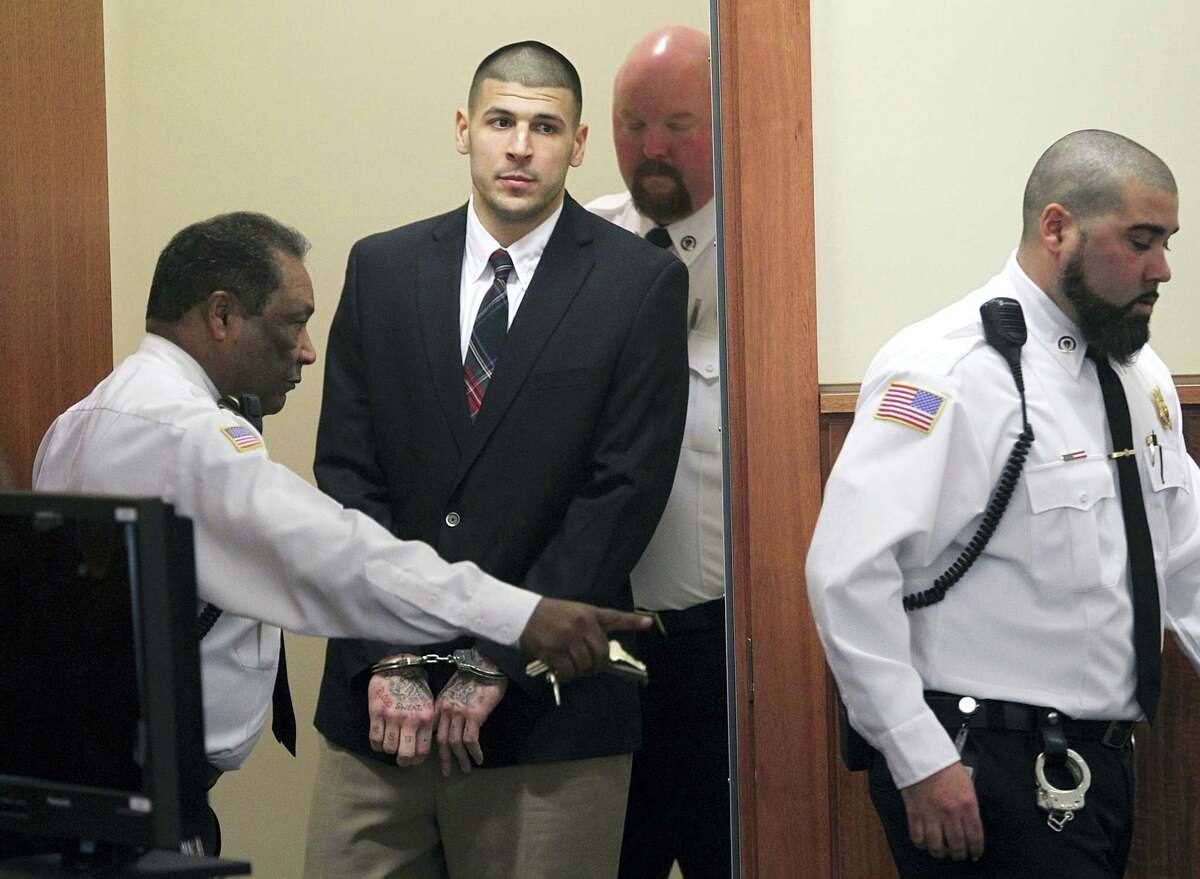 In this Monday, Dec. 23, 2013 photo, former New England Patriots NFL football player Aaron Hernandez is led into his court appearance at the Fall River Superior Court in Fall River, Mass. Massachusetts prison officials said Hernandez hanged himself in his cell and was pronounced dead at a hospital early Wednesday, April 19, 2017.