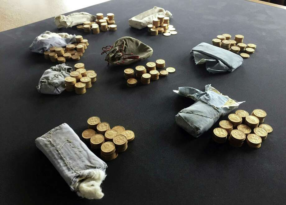 """The 913 gold coins which were found in a piano, are displayed at Ludlow Museum  in Ludlow, England  Thursday April 20, 2017, where they are being kept under lock and key. As a mystery surrounds the identity of the rightful heirs to a treasure trove of gold coins. British officials say they have been unable to trace the rightful heirs to a trove of gold coins  worth a """"life-changing"""" amount of money. The school that owns the piano and the tuner who found the gold are now in line for a windfall after a coroner investigating the find declared it treasure. Photo: Richard Vernalls/PA Via AP   / PA"""