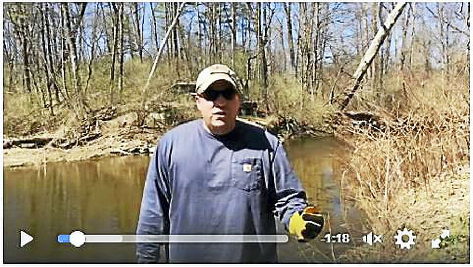 In this video screen shot, state Rep. Brian Ohler cleans up a section of the banks of the Blackberry River in North Canaan. He's challenging others to do the same in honor of Earth Day. Photo: Contributed Photo