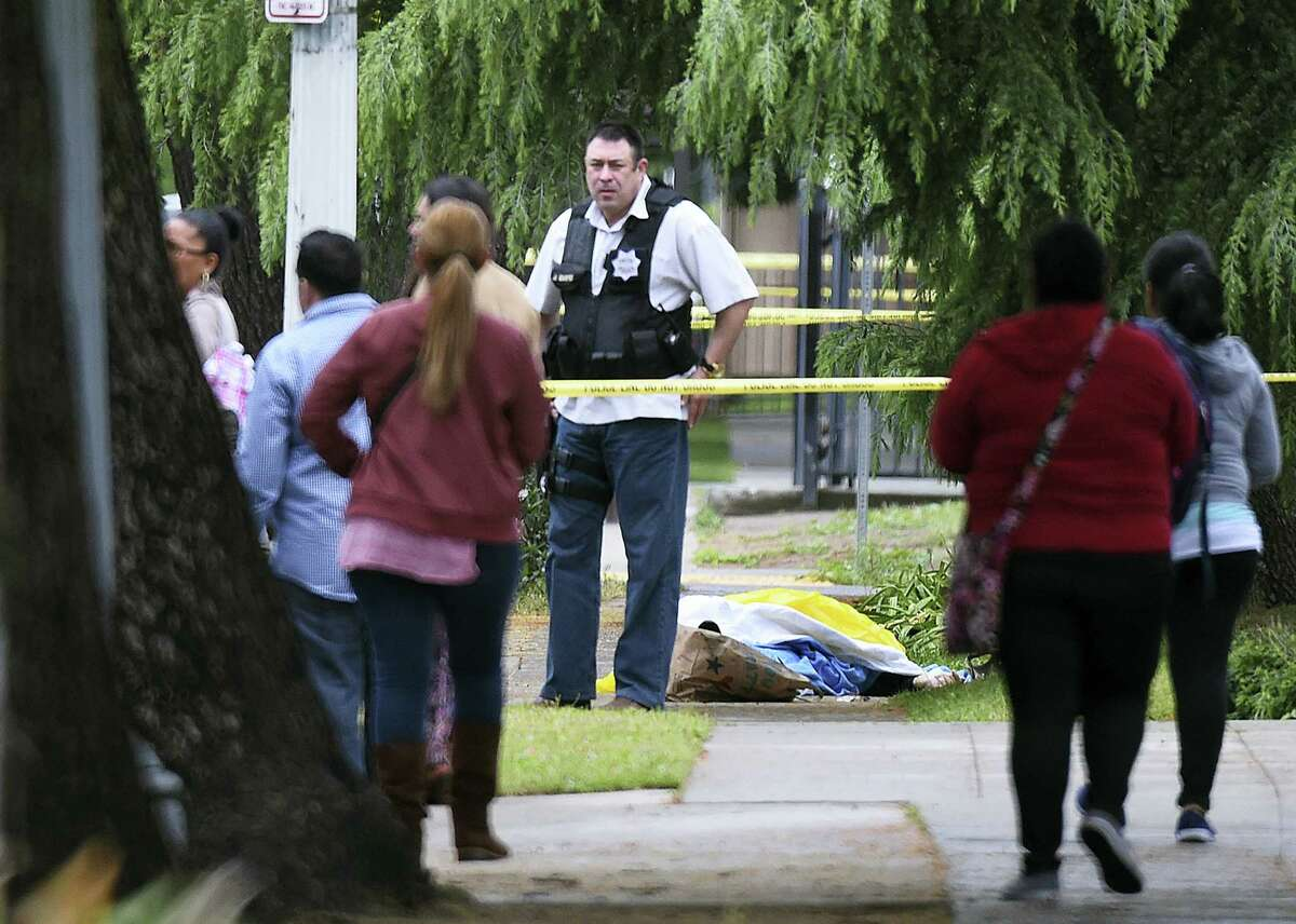 """A Fresno police detective stands over the body of one of the three shooting victims Tuesday in Fresno A man shot and killed three people on the streets of downtown Fresno on Tuesday, shouting """"God is great"""" in Arabic during at least one of the slayings and later telling police that he hates white people, authorities said. Kori Ali Muhammad, 39, was arrested shortly after the rampage, whose victims were all white, police said. He also was wanted in connection with another killing days earlier, in which a security guard was gunned down at a Fresno motel after responding to a disturbance."""