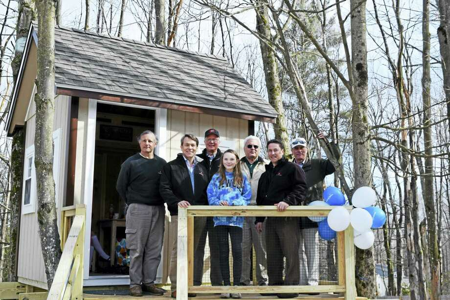 Contributed photo - Make A Wish ConnecticutAyla Fritz, center, stands on the deck of her new treehouse at her home in Colebrook. The house was a granted wish from Make A Wish Connecticut, and was brought to the Fritz's home on March 30. Photo: Digital First Media