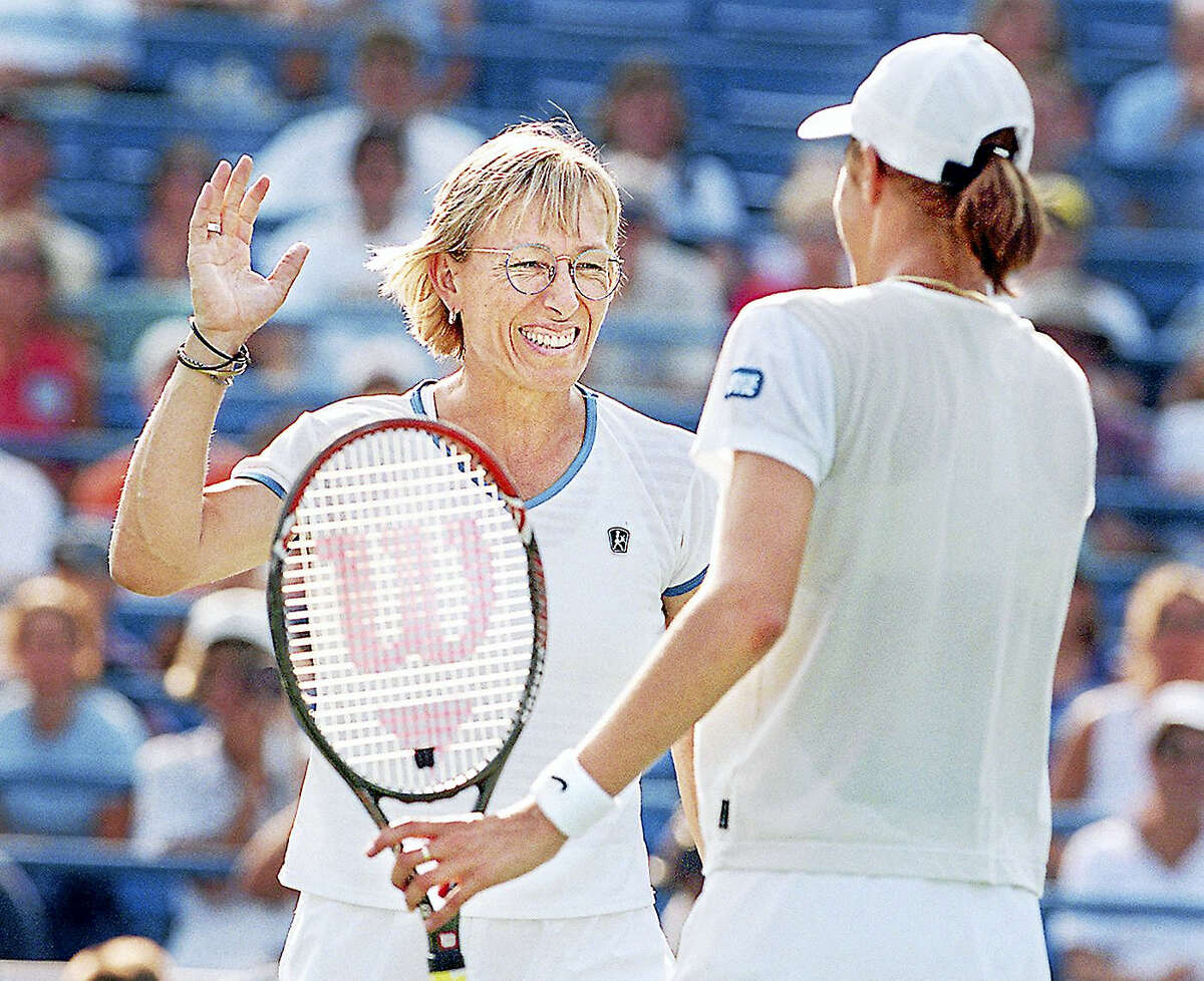 Martina Navratilova raises her hand to give her partner Katarina Srebotnik a high five during their match Thursday afternoon at the Connecticut Tennis Center.Staff Photo/Mia M. Malafronte.