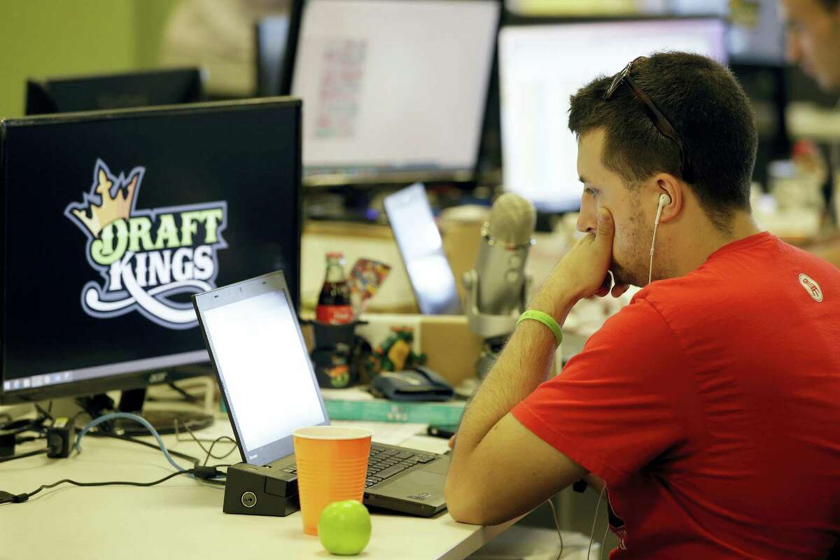 In this Sept. 9, 2015 photo, Devlin D'Zmura, a tending news manager at DraftKings, a daily fantasy sports company, works on his laptop at the company's offices in Boston. The daily fantasy sports industry has contracted starkly since questions about the legality of online games offered by companies sparked court and legislative battles across the U.S. last year.