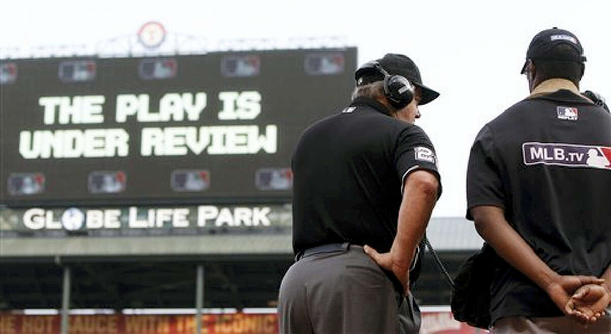 This May 16, 2015 photo shows umpire Joe West (22) connecting with MLB's review command center in New York to review Texas Rangers left fielder Delino DeShields', not pictured, attempted sliding catch of a foul ball during the first inning of a baseball game against the Cleveland Indians in Arlington, Texas. Major League Baseball umpires could start explaining replay decisions to the players and fans — the way NFL referees do — later this season if the sides can reach agreement. Under one possible scenario, the crew chief could wear a microphone beginning at the All-Star Game.