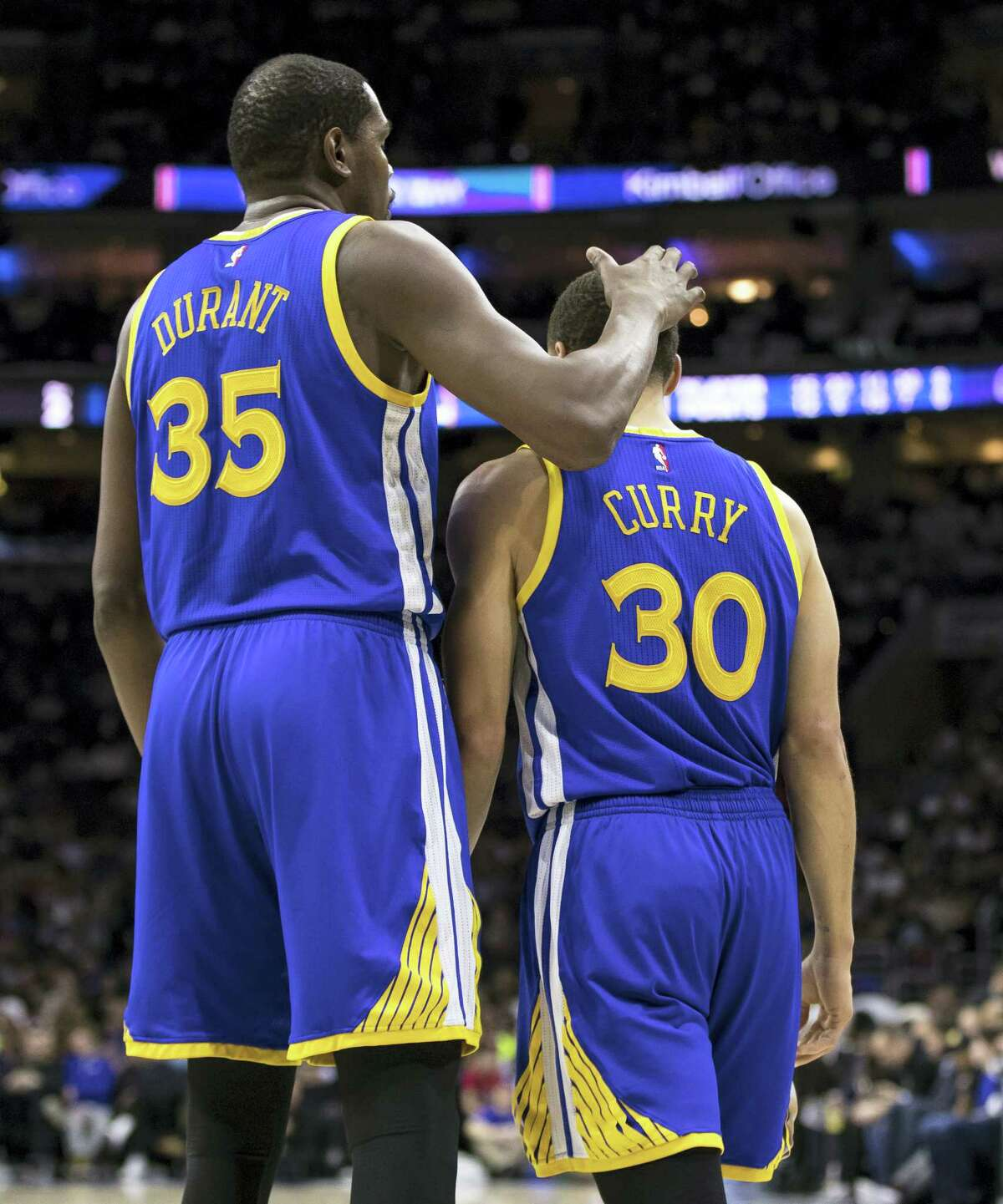 Golden State Warriors' Kevin Durant, left, pats Stephen Curry, right on the head after he misses the lay-up during the first half of an NBA basketball game against the Philadelphia 76ers on Feb. 27, 2017 in Philadelphia.