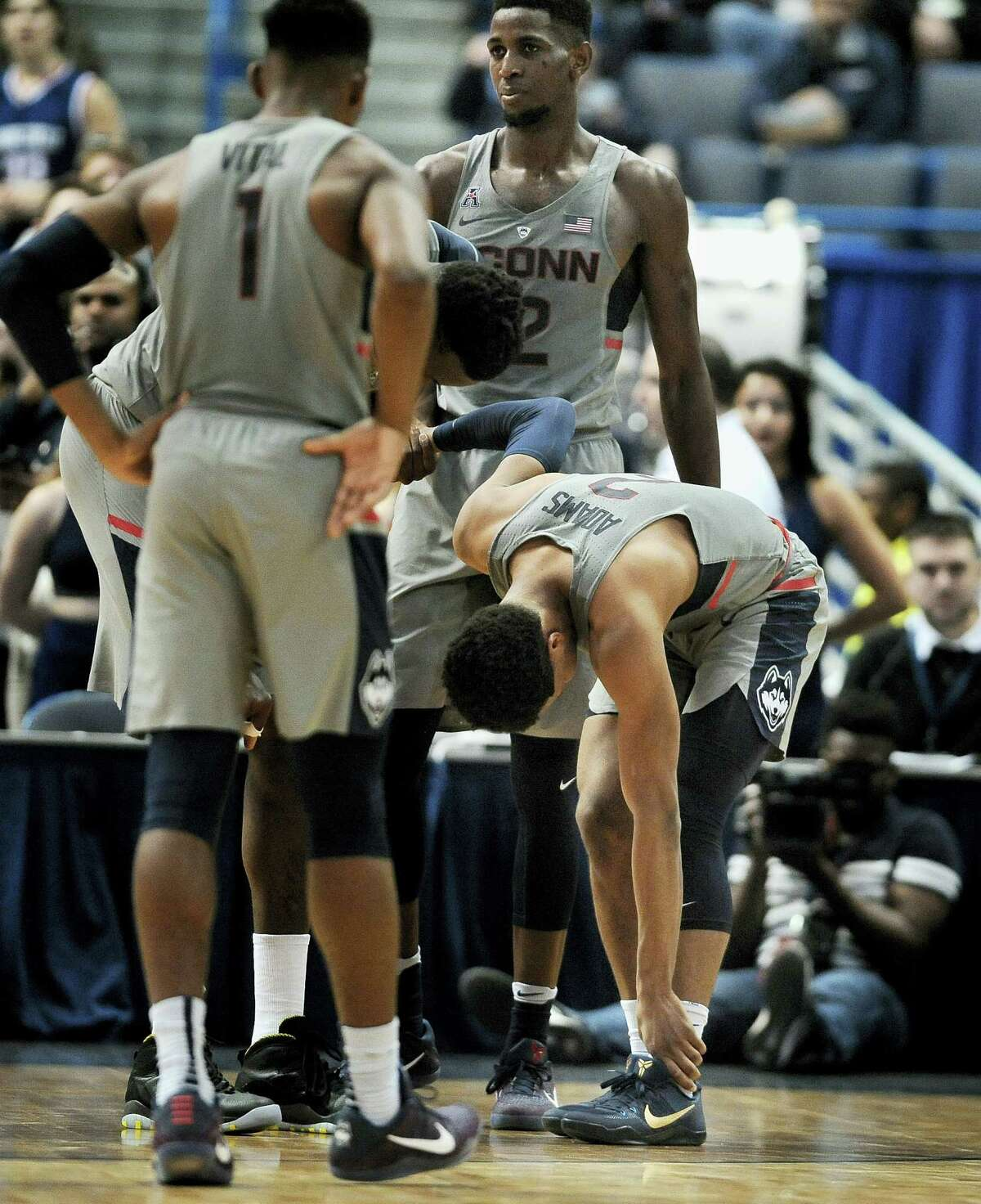 Connecticut's Jalen Adams holds his ankle as his teammates look on after becoming injured in the first half against SMU Saturday. He is expected to be a game-time decision tonight against East Carolina.