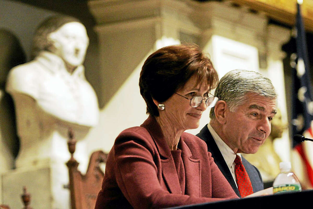 Former Massachusetts Gov. Michael Dukakis and his wife, Kitty, smile as they read letters between John Adams and his wife, Abigail, during a Massachusetts Historical Society program at Faneuil Hall in Boston.