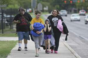 The Fletcher family goes outside to get bed rolls as Governor Greg Abbott greets evacuees as they arrive at Kazen Middle School on San Antonio's southside on August 25, 2017.  From left are Chris Fletcher , Zoe Fletcher, Temperance Fletcher and Jessica Fletcher.